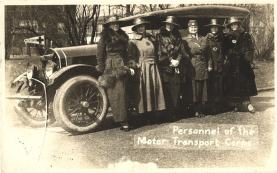 Six White female nurses standing in front of a car with a Red Cross symbol on a 'Motor Corps' flag.