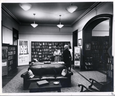 Three women stand in a high celinged room with leather couches and shelves of books.