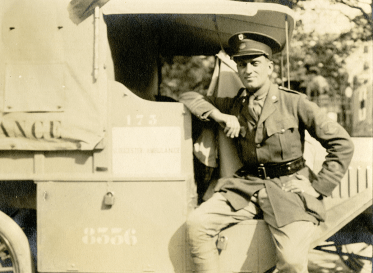 A man in uniform poses, leaning against an ambulance.