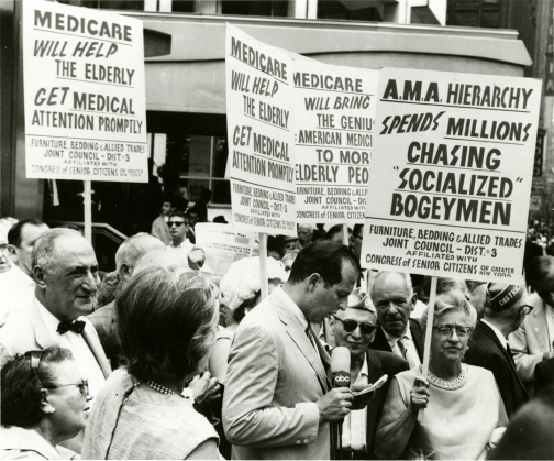 A crown of people carry signs in the street.