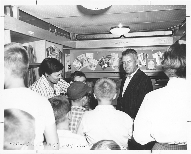 Fogarty stands in a bookmobile surrounded by young people.