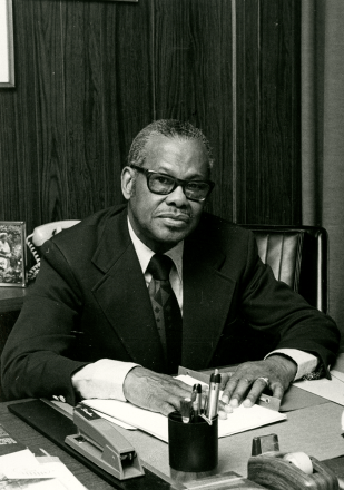 Leonidas Berry seated at a desk.