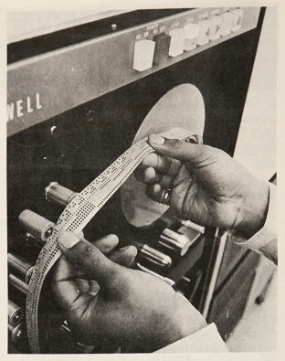 An operator feeds punched paper tape onto the reel of a machine.