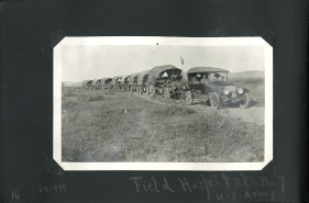 A line of 9 open covered trucks, with an American flag, stopped in a line on a dirt road.