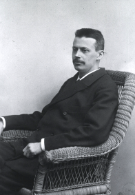 A man in a suit seated in a wicker chair.