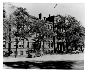 A large 5 story brick building on a city street with Trees along the curb.
