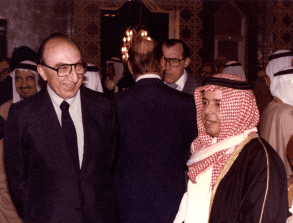 A photograph of DeBakey and a colleage in a middle eastern clothes in a room crowded with people in wester and middle eastern dress.