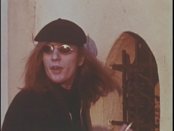 Man with long hair and Lennon glasses.