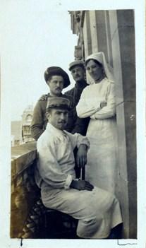 Three men and a nurse pose on a balcony.