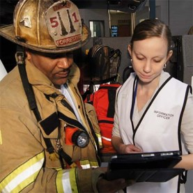 A firefighter in heavy jacket and helmet talks with the information officer