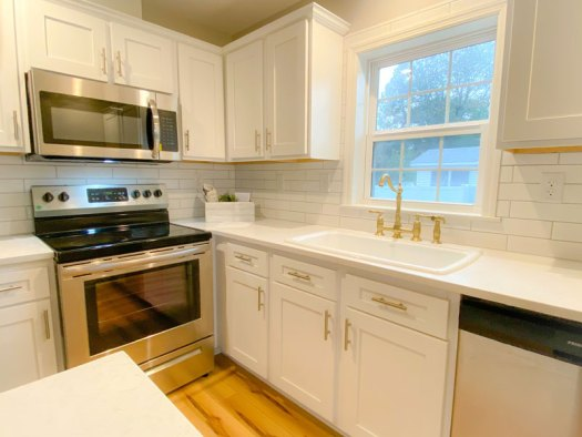 White subway tile backsplash and gold faucet highlight the brand new kitchen