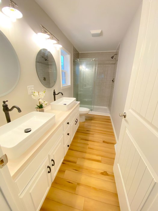Double vessel sinks and glass shower enclosure in a gorgeous master bathroom