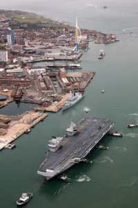 aircraft carrier surrounded by tug boats in Portsmouth harbour