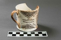 "Whiteware transfer-printed ""Poor Richard's Almanac"" mug from VanDeventer-Fountain House. Printed on this side: ""Being Lessons for Youth on Industry Temperance Diligence Frugality"" (Photo by Norm Eggert for NMSC)"