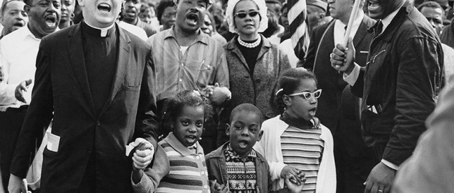 Dr. Martin Luther King, Jr., was a champion for equity in education. Civil Rights Movement co-founder Dr. Ralph David Abernathy and his wife Mrs. Juanita Abernathy (not pictured) follow with Dr. and Mrs. Martin Luther King, Jr., as the Abernathy children march on the front line, leading the Selma to Montgomery March in 1965. The children are (left-right): Donzaleigh Abernathy in striped sweater, Ralph David Abernathy III, and Juandalynn R. Abernathy in glasses. Name of the White Minister in the photo is unknown. (Abernathy Family Photos/Wikipedia Commons)