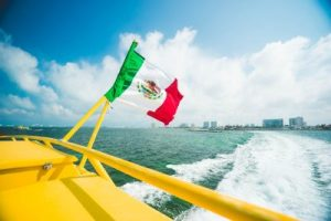 Mexican flag on yellow boat sailing on water