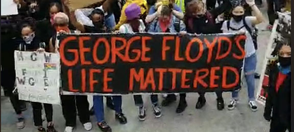 Image of protestors holding a sign reading George Floyd's Life Mattered