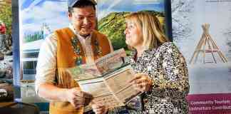 Bobby Drygeese, owner of B. Dene Adventures and Cathie Bolstad CEO of NWT Tourism look at a program for the 2018 NWT Tourism Annual General Meeting (AGM) and Conference. Meaghan Richens/NNSL photo