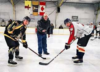 Jim MacDonald drops the puck between Sidney Nichol of the Rankin Rock and Andrew Pearce of the Baffin Blizzard to mark the championship game of the Polar Bear Plate juvenile-junior tournament in Rankin Inlet on Feb. 17, 2019. Photo courtesy Noel Kaludjak