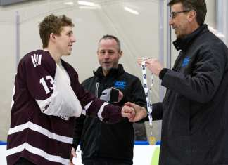Jacob Schofield, sling and all, accepts his gold medal from Mark Kosak, chief executive officer of the Alberta Colleges Athletics Conference (ACAC), after the MacEwan Griffins men's hockey team won its third consecutive ACAC title in Edmonton on Saturday. Matthew Jacula/MacEwan Athletics photo