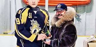 Garren Voisey of the Rankin Rock is presented with the Best Defenceman Award by Hockey Nunavut president Mike McPherson at the Nunavut Territorial Bantam Hockey Championship in Arviat on March 17, 2019. Photo courtesy Gleason Uppahuak