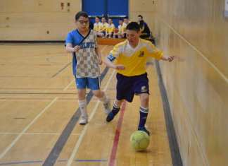 Kugluktuk's Jonathon Ihumatak tries to shield the ball from an Inuvik Wolves player during Grade 6 boys division playoff action at Junior Super Soccer in Yellowknife on April 28. James McCarthy/NNSL photo