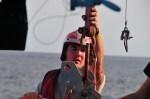 Man wearing a helmet holding onto a pole