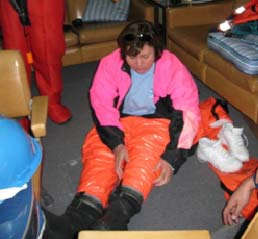 Donning the survival suit is necessary if you are forced to abandon ship in cold water.  The suit must be donned quickly. This is not an easy task, but I was successful.  Now, please step aside so that I can make my way to life raft number 10 on the port side of the ship!