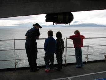 A crewmember of the Rainier gives children a tour of the ship.