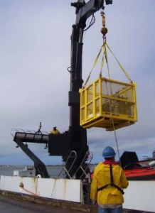 Loading the scientists' equipment onto the FOSTER using the ship's deck crane
