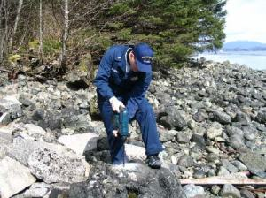 Ensign Matthew Glazewski drills to establish a benchmark on Noyes Island, AK.