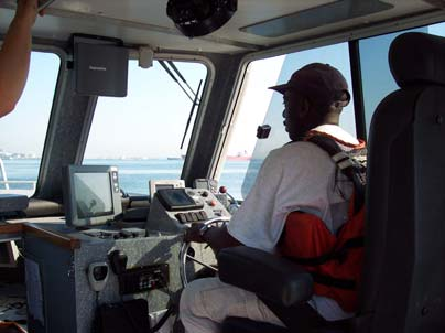 Bernard Pooser behind the wheel of the launch. The route he drives in the harbor is very specific, and he must follow careful 'driving lines' that the surveyor also sees on one of the four computer screens inside of the launch.  This job is much easier said than done, a real challenge!