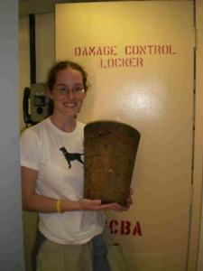 TAS Jill Carpenter holding a damage control plug used to plug a hole in the hull of a ship.