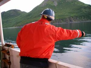 "Seaman Surveyor Erik Davis signals ""Stop"" with a closed fist while boat RA-3 is being lowered to the water."