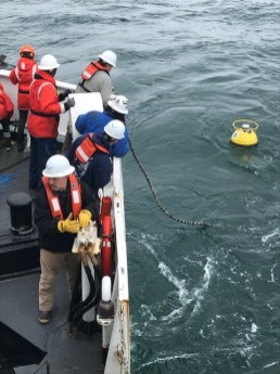 The Fairweather team works together to launch a tide buoy in the Arctic Ocean
