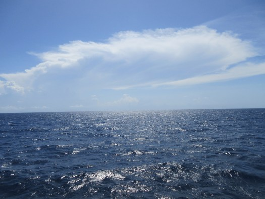 Clouds over shining water and the horizon