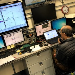"""Scientist Dezhang Chu communicates with the team at the down riggers on where to move the """"magic sphere"""" for calibration"""