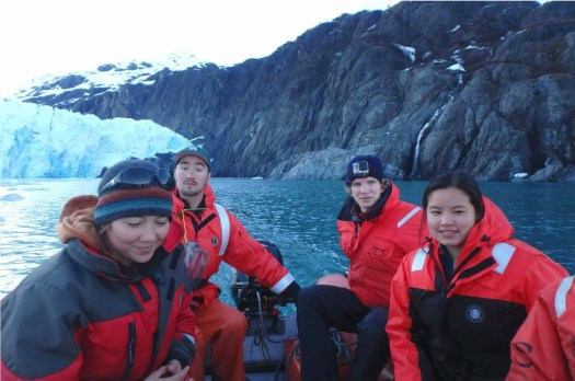 Four scientists, wearing protective float coats, ride on a small motorboat  closer to the glacier