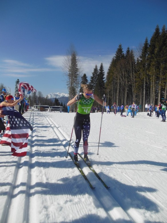 Sadie Bjornsen Racing by Wall of American Flags in Sochi Olympics Relay