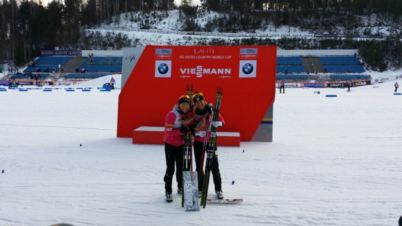 Sophie Caldwell and Kikkan Randall in Front of World Cup Podium Lahti 2014