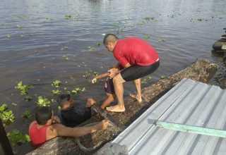 Momento em que os bombeiros retiram o corpo da criança da água. / Foto : Divulgação