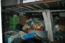 Piles of debris and junk on the side of the house