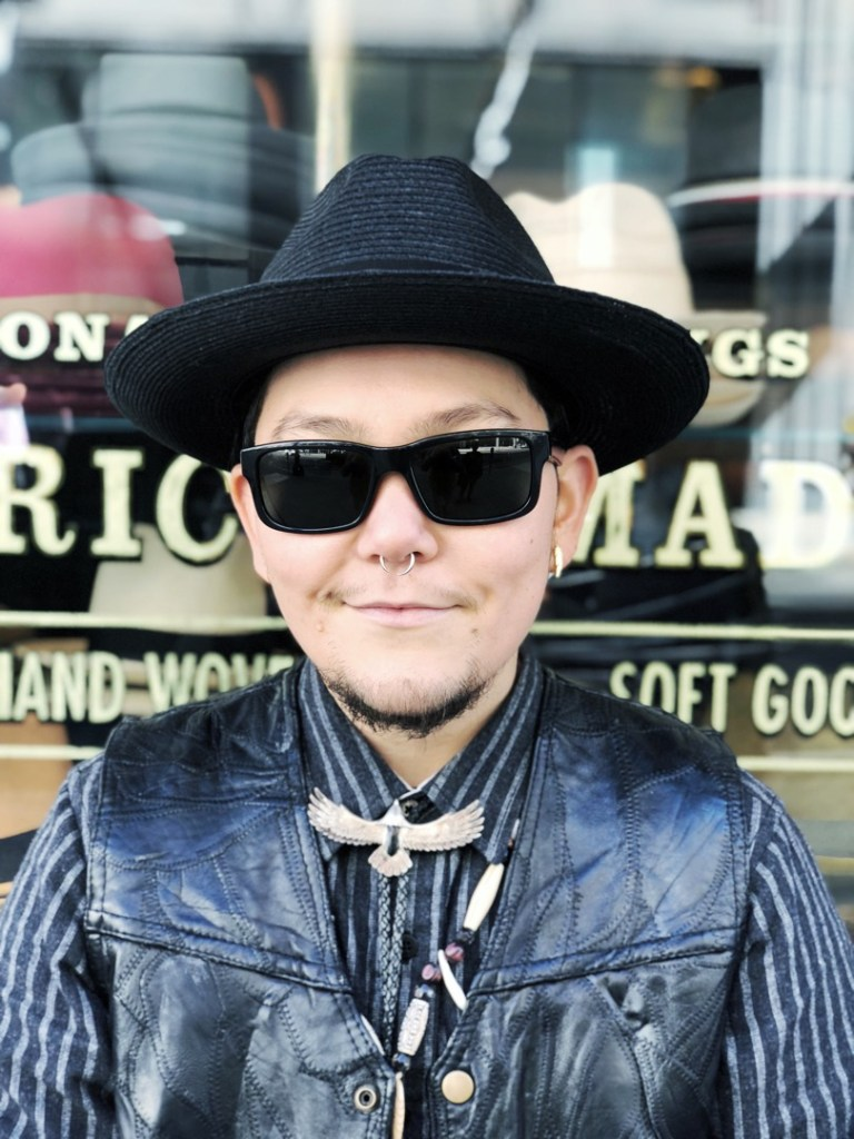 """Rosco Kickstone was working retail when he caught our eye through the window of a Union Square hat shop. His style is informed by his identity: A Southwestern, psychedelic, surf metal musician. """"The clothes I wear are inspired by my culture, but I like to throw in the modern flair. When I'm performing on stage, I want to look good.""""  Hat: Goorin Bros. Hat Shop; Necklace: Handmade; Boots: Doc Martens; the rest: Thrift finds"""