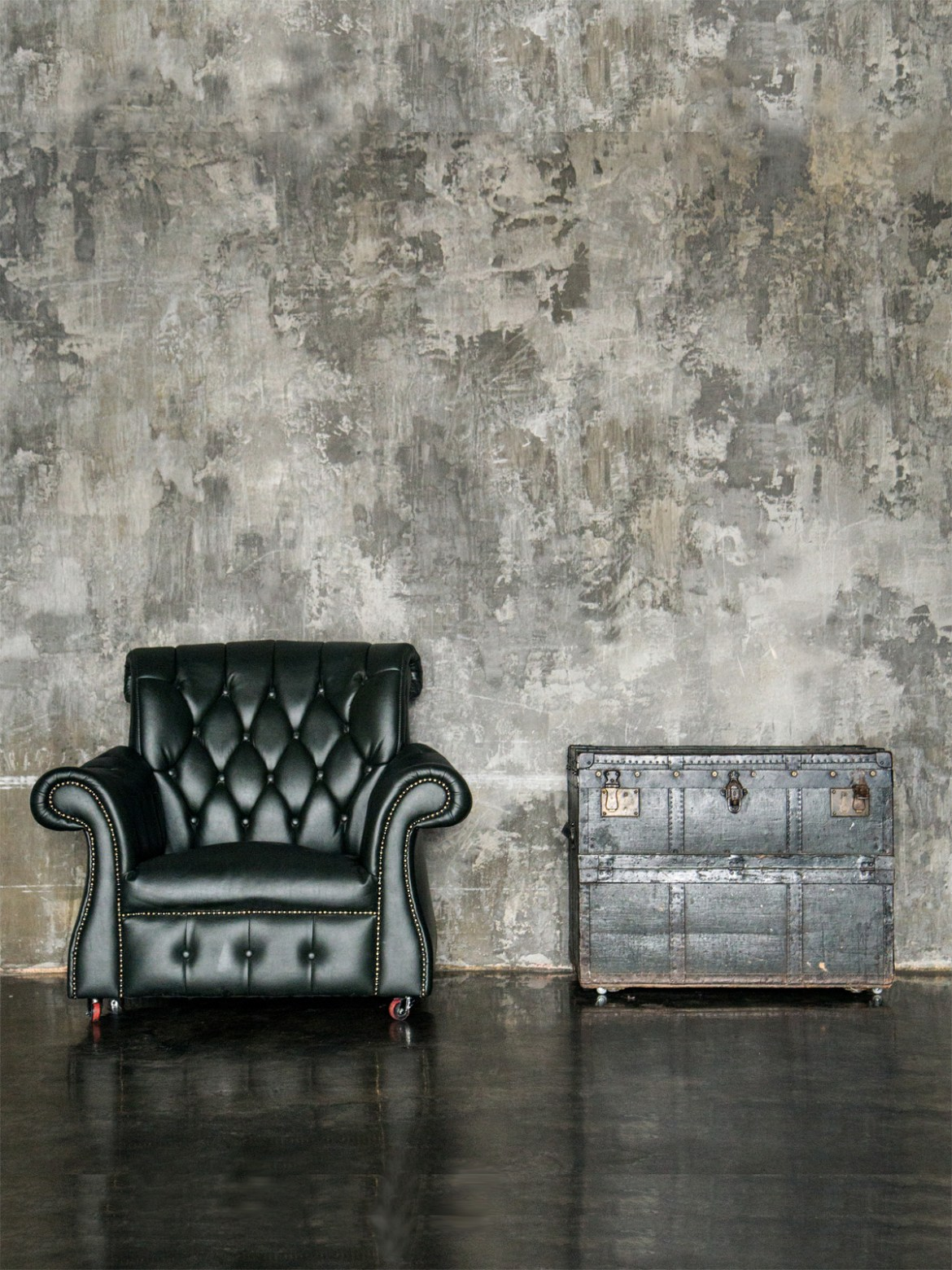 black leather chair and antique trunk with grunge textured wall