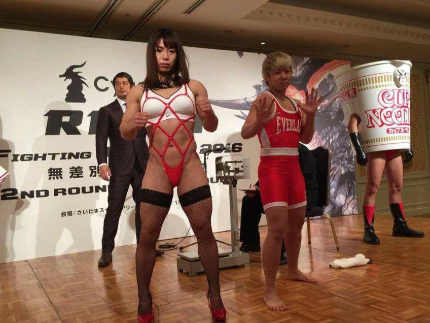 """Momento curioso da pesagem do RIZIN 3. Rin Nakai mostra suas curvas em traje bastante """"revelador"""" enquanto confirma seu peso para duelo contra Kanako Murata. Momento este, captado pelo """"Cup Noodles"""" gigante à direita... (Foto: RIZIN FF)"""