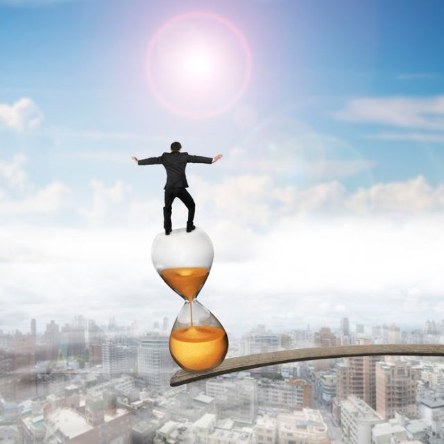 46496240 - businessman balancing hourglass on edge of wooden plank, with sun sky cityscape background.