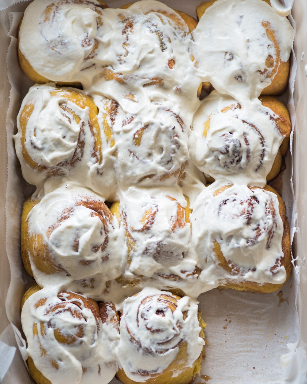 top down view of frosted/iced pumpkin cinnamon rolls