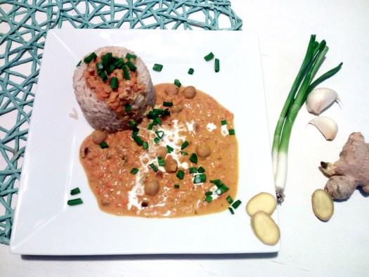 """Viereckiger weißer Teller mit einer geformten Hügel aus Reis und dazu eine gelbe Kokos-Currysoße mit Kichererbsen und roten Linsen - nennt sich """"Sun Down"""". Neben den Teller befindet sich eine Frühlingszwiebel, zwei Knoblauchzehen und eine Ingwer-Wurzel mit einzelnen Scheiben."""