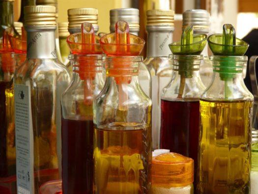 Mehere Flaschen aus Glas mit verschieden Ölen, Essig und Vinaigrette