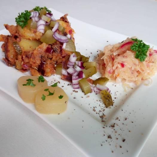 Bronze-Goldene heiße Bratkartoffeln, mit roten Zwiebeln, frischer Petersilie, knackigen Gewürzgurken und warmen süßlichen Sauerkraut mit zarten Paprikastreifen